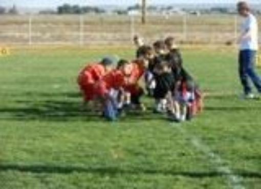 A group of kids huddle during football