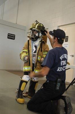 A firefighter helps a young person try on firefighting gear