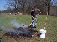 A person tends to a controlled fire in a yard