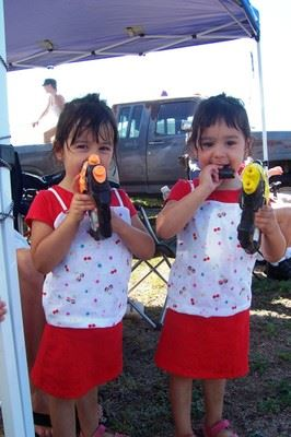 Twin girls hold squirt guns